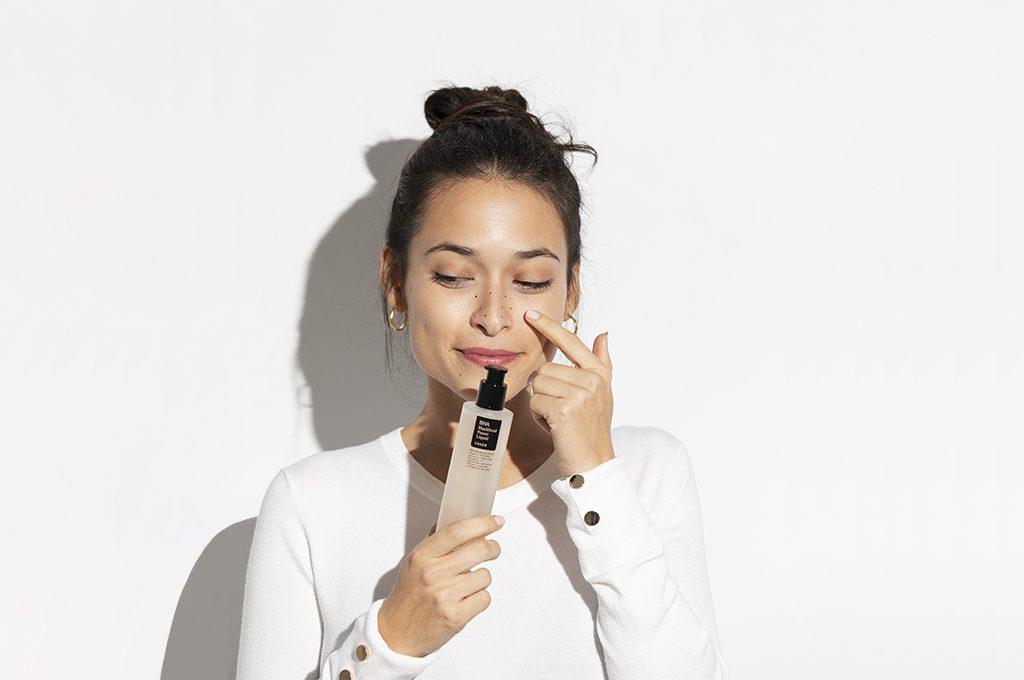Frau hält ein Kosmetikprodukt in der Hand
