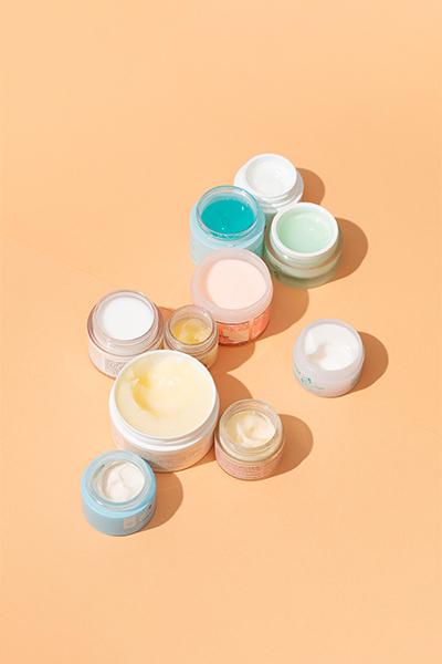Mehrere Kosmetiktiegel auf farbigem Hintergrund.