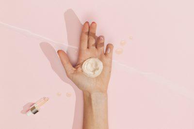 Hand einer Frau, auf der sich eine Creme befindet